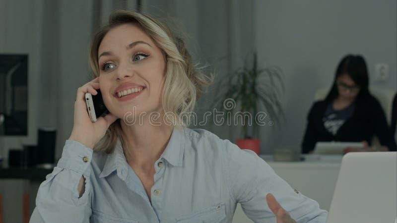 Giovane donna sorridente che si siede alla scrivania e che parla sul telefono cellulare fotografie stock libere da diritti