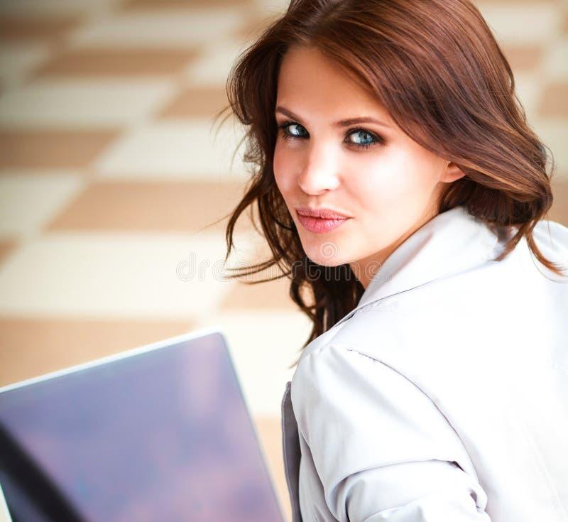 Giovane donna sorridente che si siede con il computer portatile fotografie stock