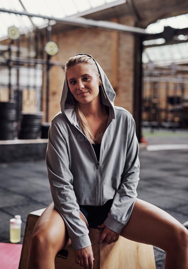 Giovane donna sorridente che si siede in una palestra dopo avere risolto fotografia stock