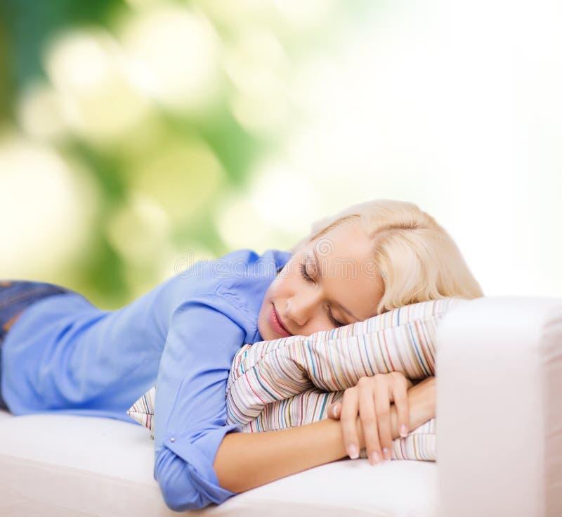 Giovane donna sorridente che si trova sul sofà fotografia stock libera da diritti