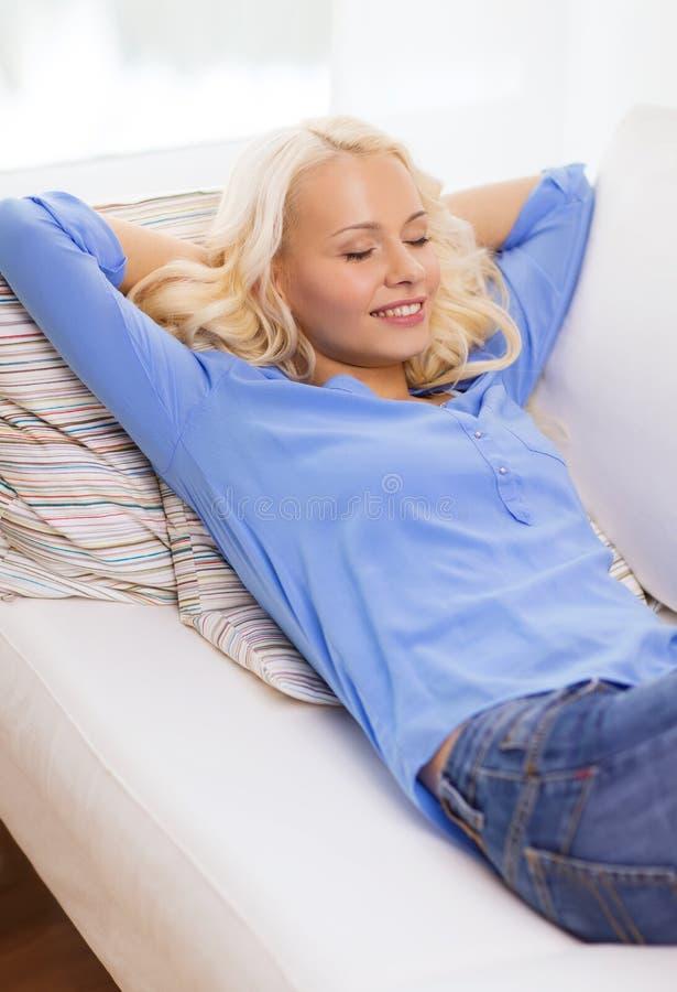 Giovane donna sorridente che si trova sul sofà a casa immagine stock