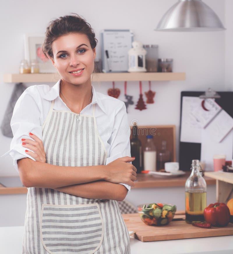 Giovane donna sorridente che sta nella cucina fotografia stock libera da diritti