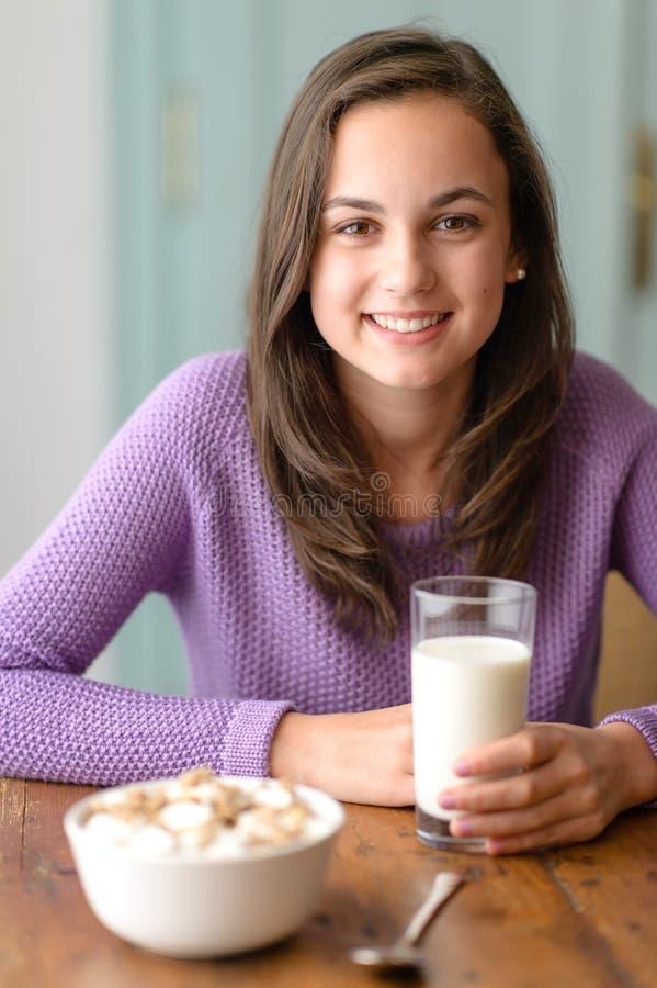Giovane donna sorridente che tiene bicchiere di latte immagini stock