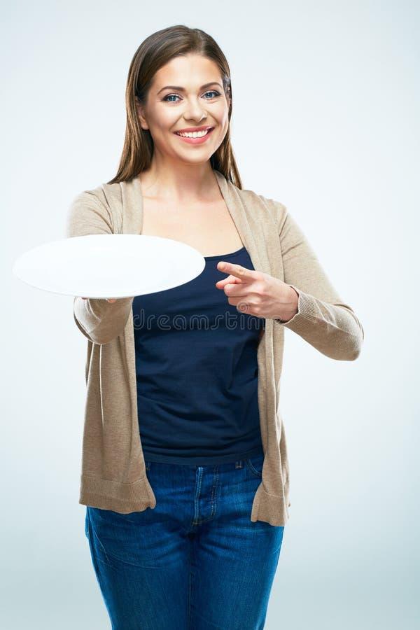Giovane donna sorridente che tiene indicare vuoto del dito e del piatto immagini stock libere da diritti