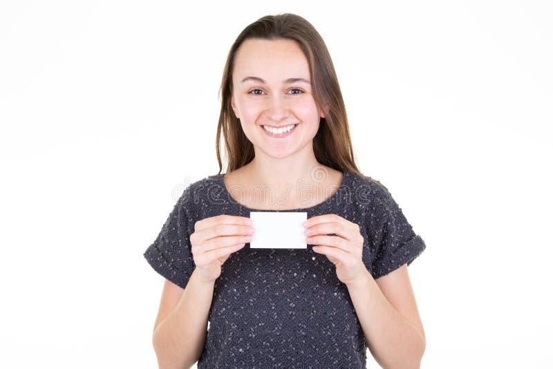 Giovane donna sorridente che tiene la carta vuota bianca dello spazio in bianco in sua mano con lo spazio della copia per testo fotografie stock