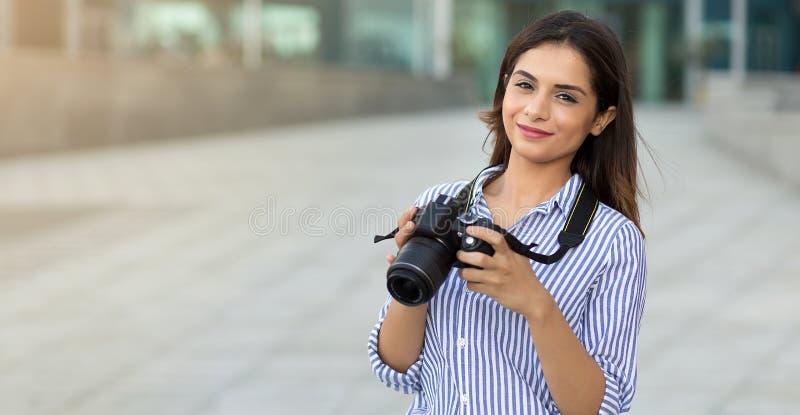 Giovane donna sorridente che tiene la macchina fotografica all'aperto con lo spazio della copia Fotografo, turista fotografia stock libera da diritti