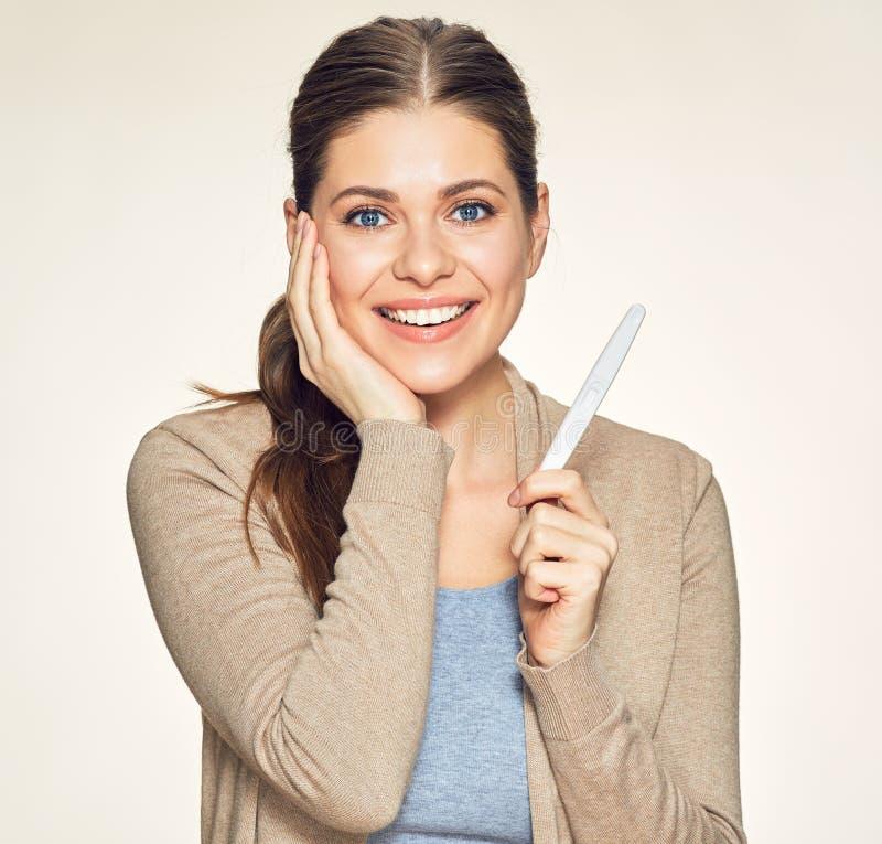Giovane donna sorridente che tiene prova incinta fotografie stock libere da diritti
