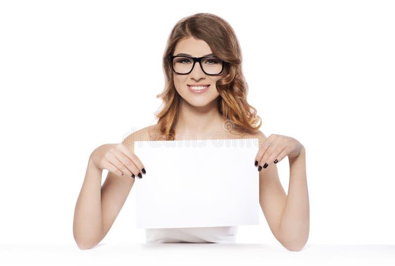 Giovane donna sorridente che tiene segno bianco in bianco immagini stock libere da diritti