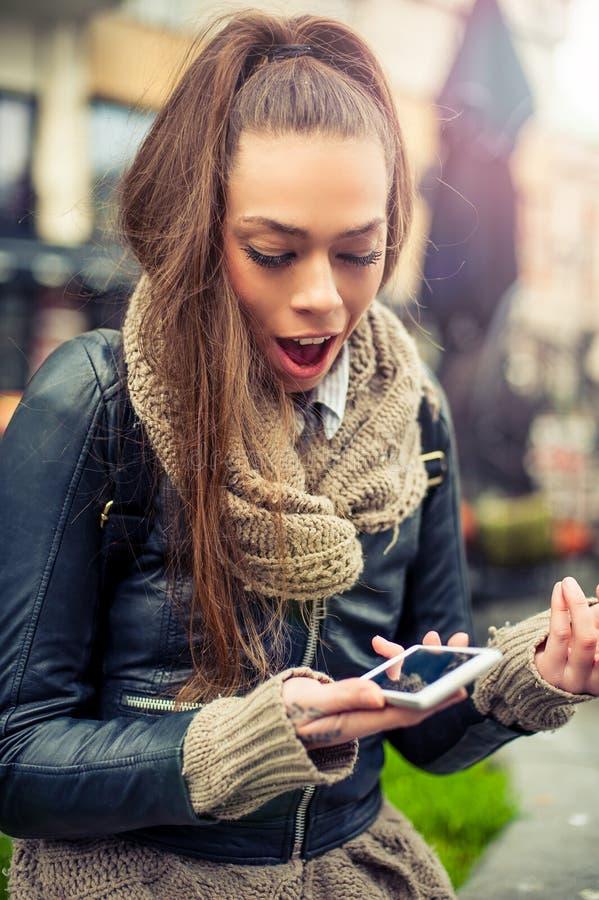Giovane donna sorridente che usando cellulare sulla via fotografie stock libere da diritti