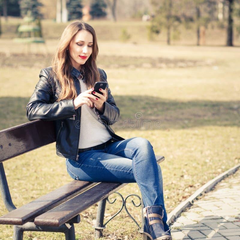 Giovane donna sorridente che utilizza smartphone nel parco fotografia stock