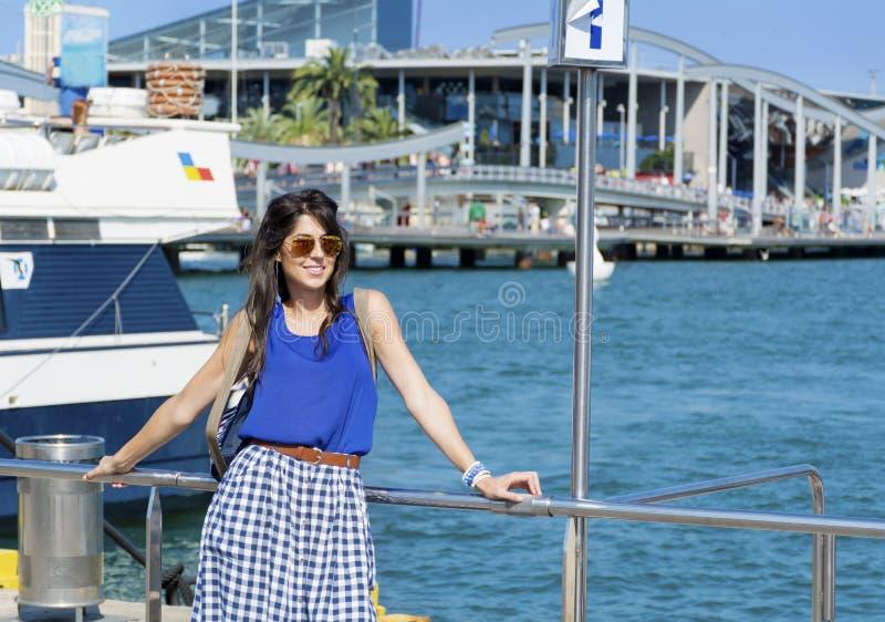 Giovane donna sorridente con gli occhiali da sole dorati che si siedono su un pilastro del mare a Barcellona fotografia stock