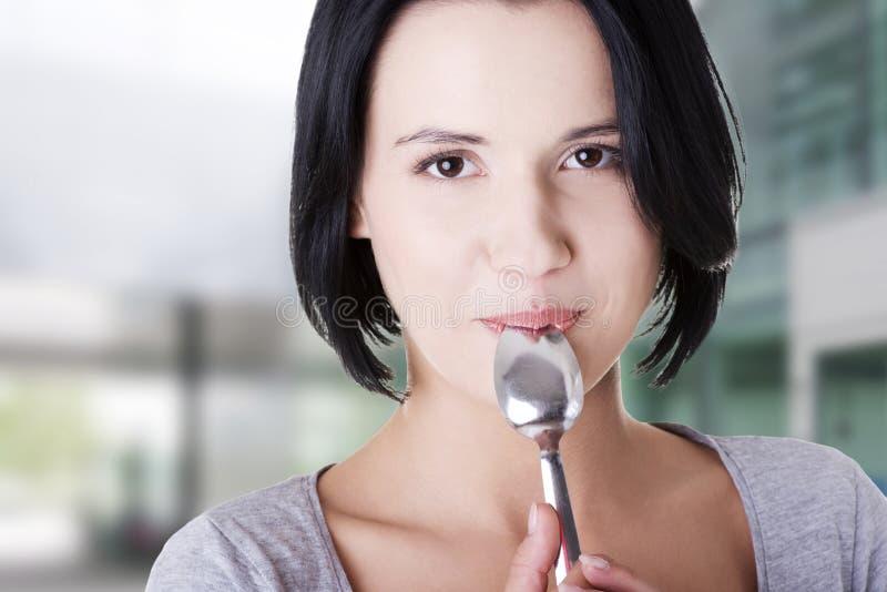 Giovane donna sorridente con il cucchiaio immagine stock libera da diritti