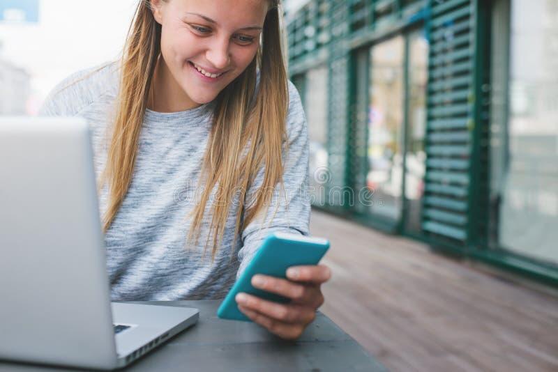 Giovane donna sorridente con il telefono cellulare ed il computer portatile che funzionano in caffè all'aperto immagini stock libere da diritti