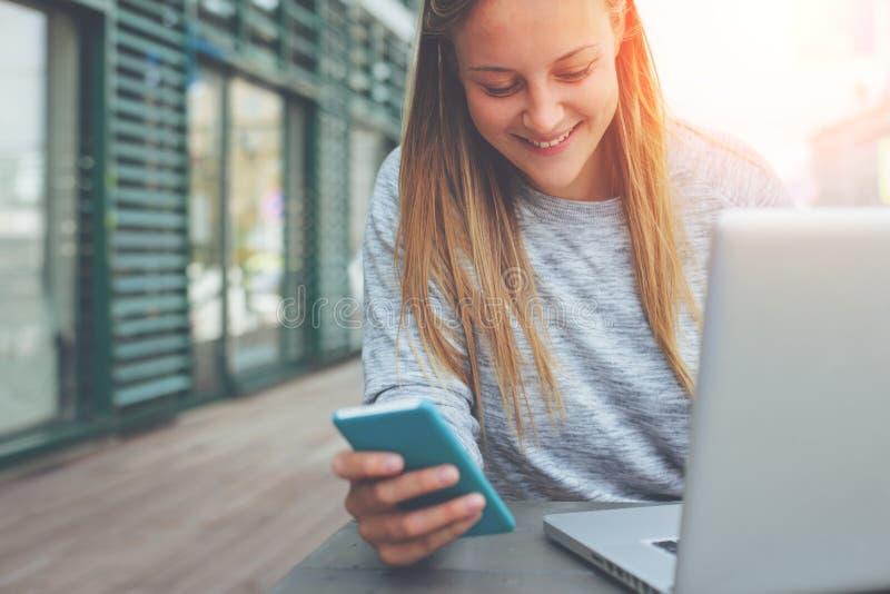 Giovane donna sorridente con il telefono cellulare in sua mano che lavora al computer portatile in caffè della via immagini stock libere da diritti