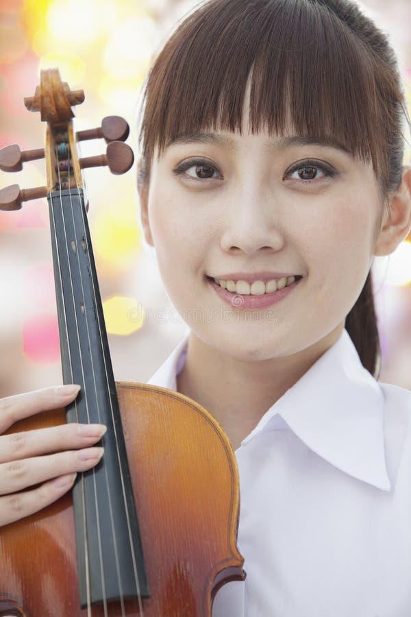 Giovane donna sorridente con il violino, esaminante macchina fotografica, ritratto fotografia stock