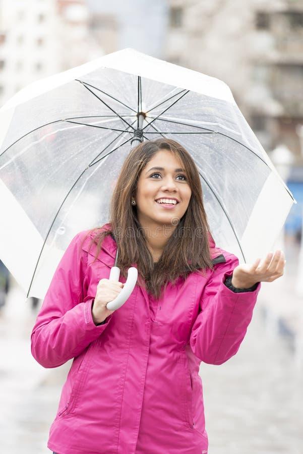 Giovane donna sorridente con l'ombrello che controlla per vedere se c'è la pioggia fotografie stock libere da diritti
