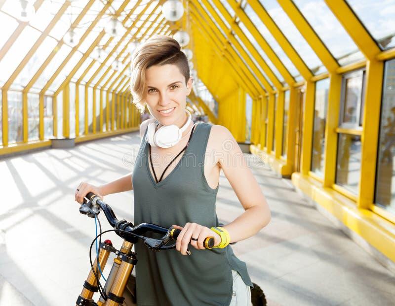 Giovane donna sorridente con la bicicletta nel passaggio pedonale immagine stock