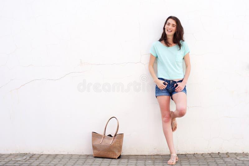Giovane donna sorridente con la borsa che pende contro la parete bianca fotografia stock
