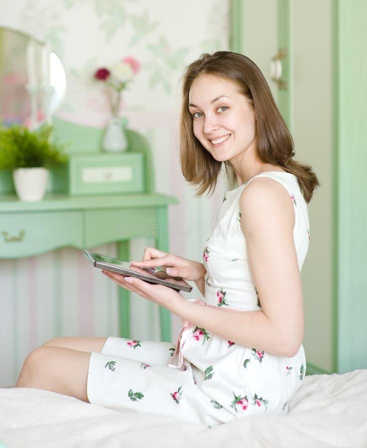 Giovane donna sorridente con la compressa fotografia stock libera da diritti