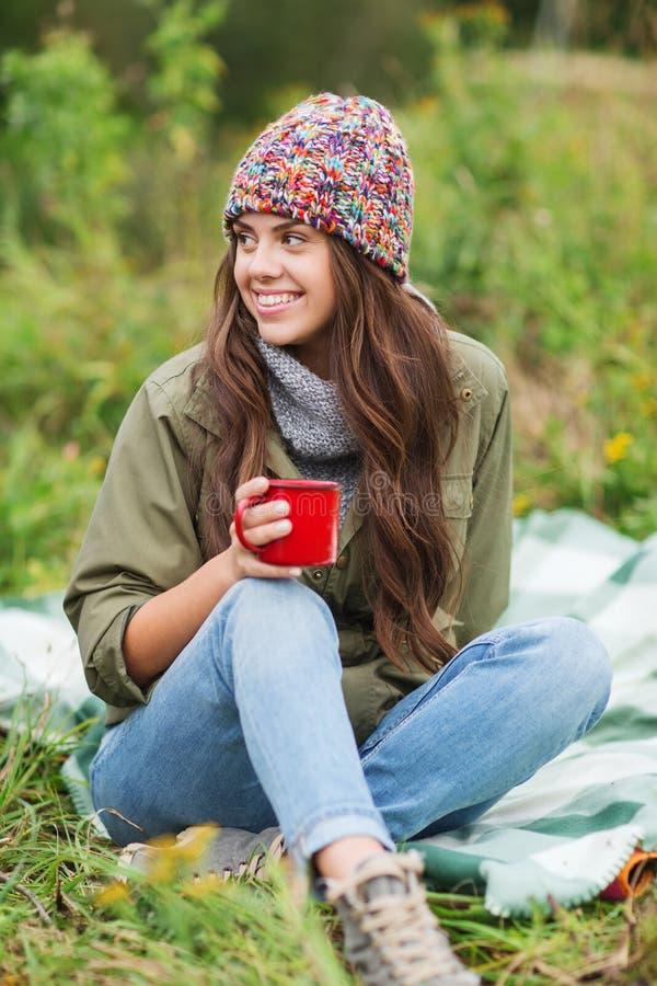 Giovane donna sorridente con la tazza che si siede nel campeggio fotografia stock