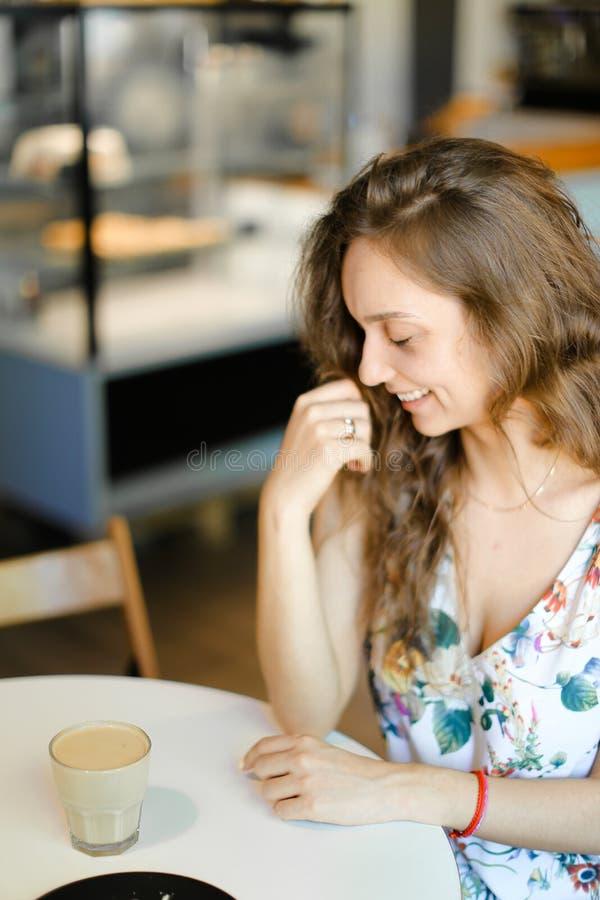 Giovane donna sorridente con la tazza di caffè che si siede al caffè ed al riposo fotografie stock