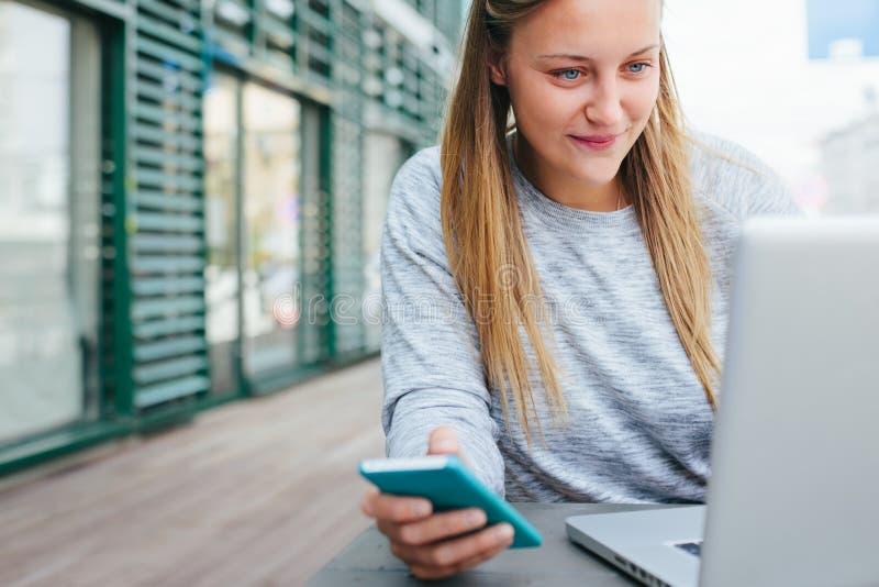 Giovane donna sorridente con lo smartphone ed il computer portatile che funzionano in caffè all'aperto, email della lettura delle immagini stock