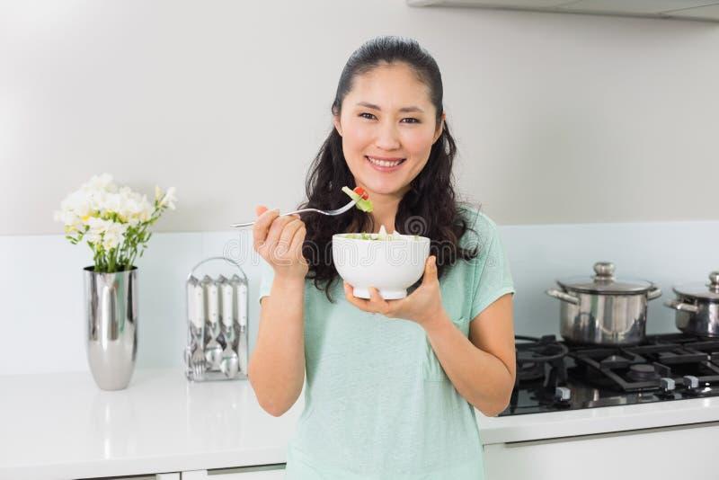 Giovane donna sorridente con una ciotola di insalata in cucina immagine stock libera da diritti