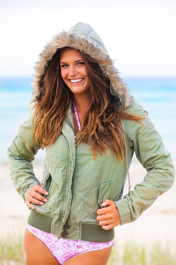 Giovane donna sorridente in costume da bagno e cappotto incappucciato fotografie stock libere da diritti