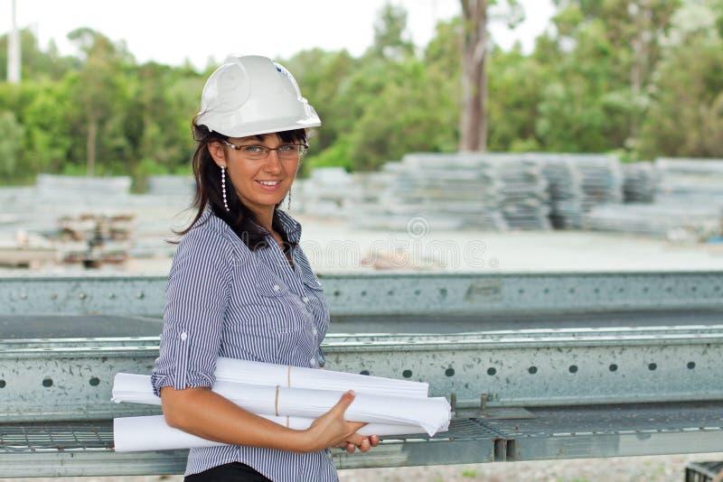 Giovane donna sorridente dell'assistente tecnico con le illustrazioni rotolate fotografia stock