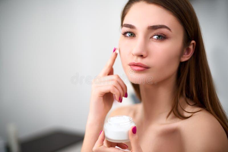 Giovane donna sorridente della corsa mista che applica la crema di fronte sulla sua pelle perfetta Modello con pelle perfetta che fotografie stock libere da diritti