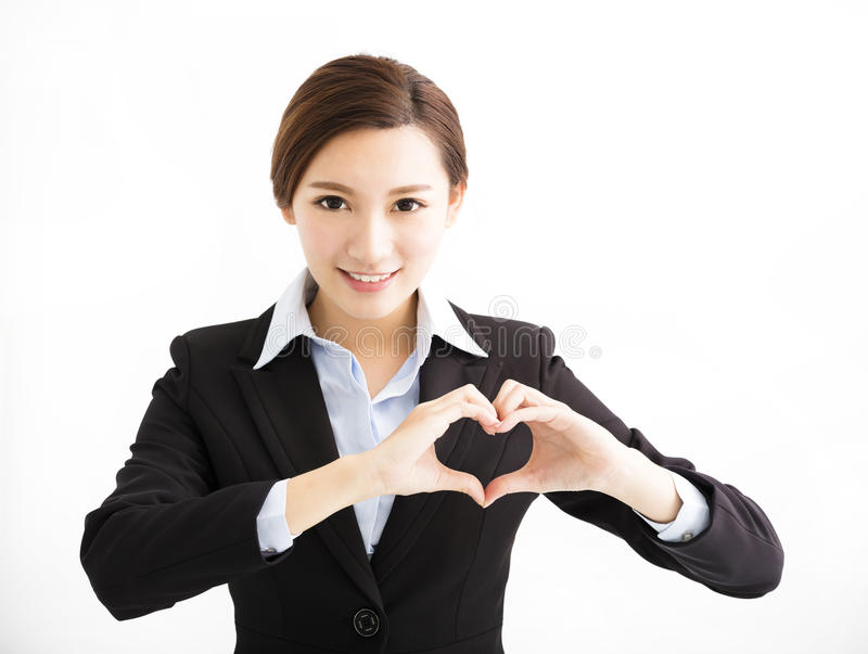 Giovane donna sorridente di affari che fa forma del cuore fotografia stock libera da diritti