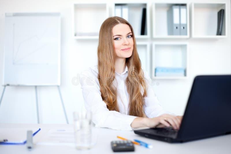 Giovane donna sorridente di affari che lavora al computer portatile fotografia stock