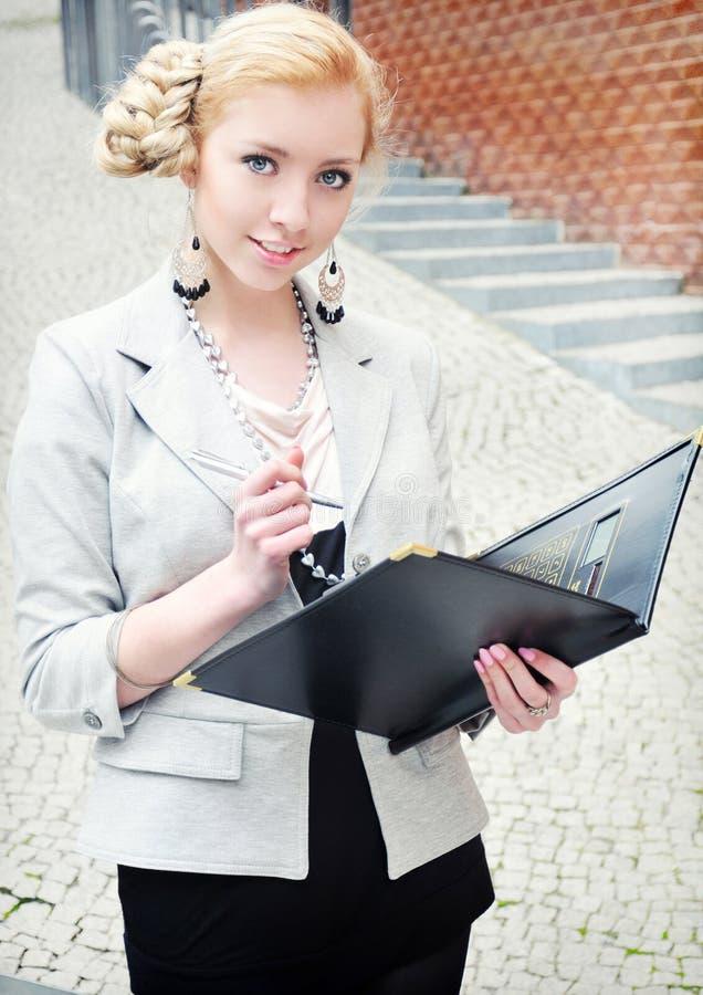Giovane donna sorridente di affari con il dispositivo di piegatura in mani fotografia stock