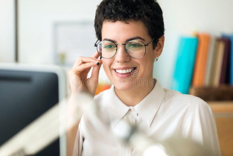 Giovane donna sorridente di affari facendo uso delle sue carte bianche per fare una chiamata mentre lavorando con il suo computer fotografia stock