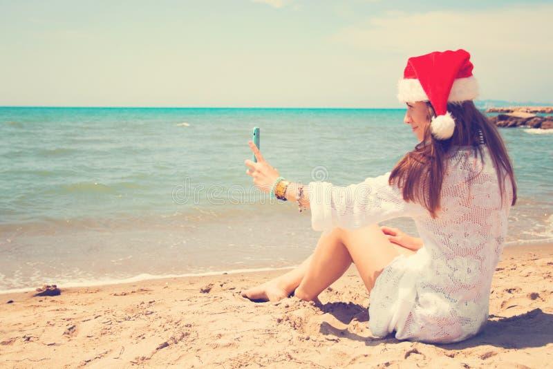 Giovane donna sorridente di Natale in cappello rosso di Santa che prende l'autoritratto dell'immagine sullo smartphone alla spiag immagine stock