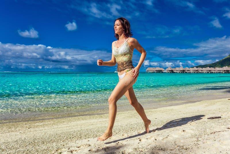Giovane donna sorridente divertendosi sulla spiaggia tropicale immagini stock