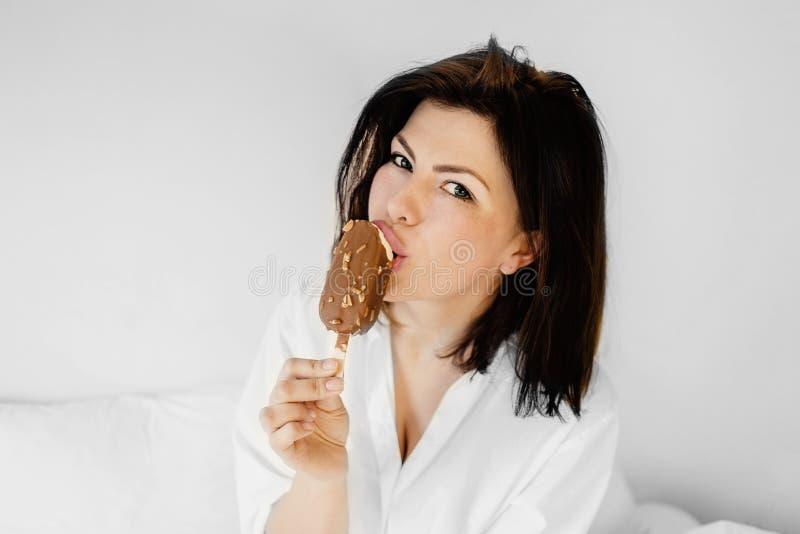 Giovane donna sorridente felice che mangia il gelato in una camera da letto Beautif immagine stock libera da diritti