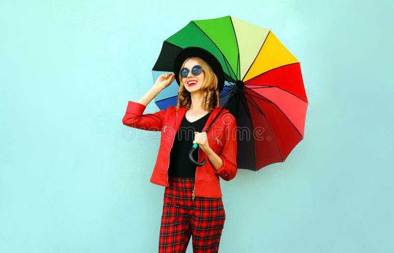 Giovane donna sorridente felice che tiene ombrello variopinto in mani, rivestimento rosso d'uso, black hat sulla parete blu immagini stock libere da diritti