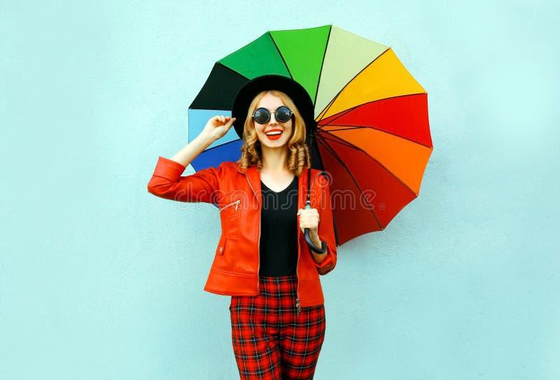Giovane donna sorridente felice che tiene ombrello variopinto in mani, rivestimento rosso d'uso, black hat sulla parete blu fotografia stock