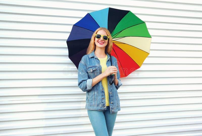 Giovane donna sorridente felice che tiene ombrello variopinto in mani su bianco immagini stock