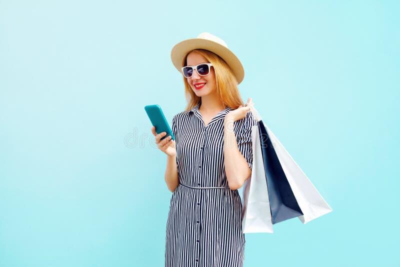Giovane donna sorridente felice con il telefono, tenente i sacchetti della spesa variopinti in cappello di paglia del giro di est immagini stock libere da diritti