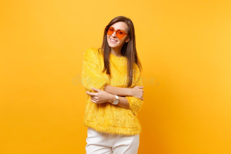 Giovane donna sorridente graziosa in maglione della pelliccia, pantaloni bianchi, occhiali arancio del cuore tenentesi per mano p fotografie stock libere da diritti