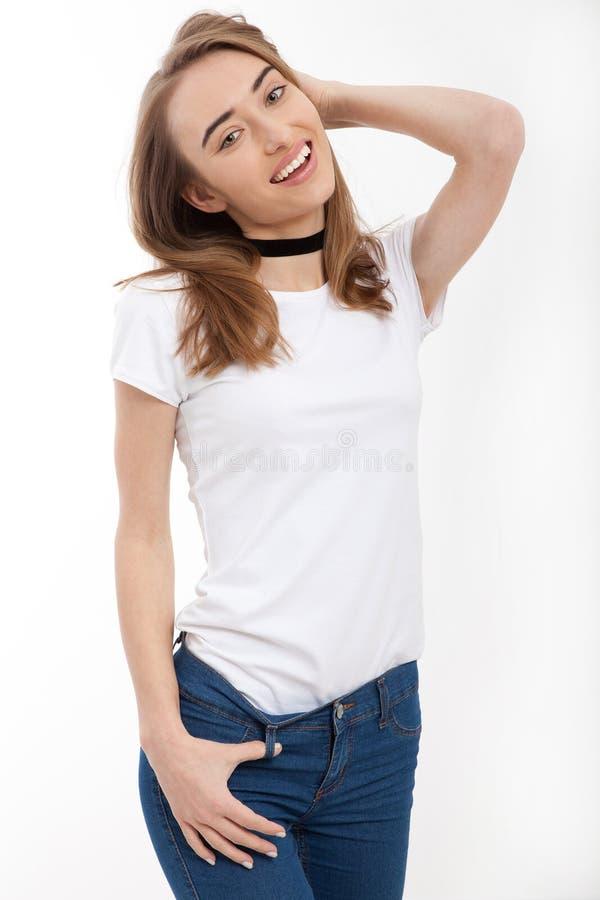 Giovane donna sorridente in maglietta bianca dello spazio in bianco del modello con lo spazio della copia su fondo bianco Front V fotografia stock libera da diritti