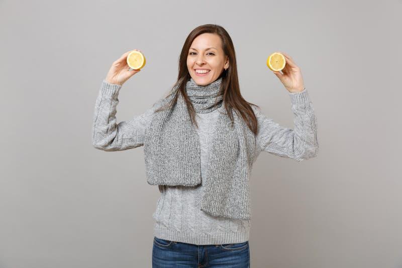 Giovane donna sorridente in maglione grigio, sciarpa che giudica i limoni isolati sul ritratto grigio dello studio del fondo dell fotografia stock libera da diritti