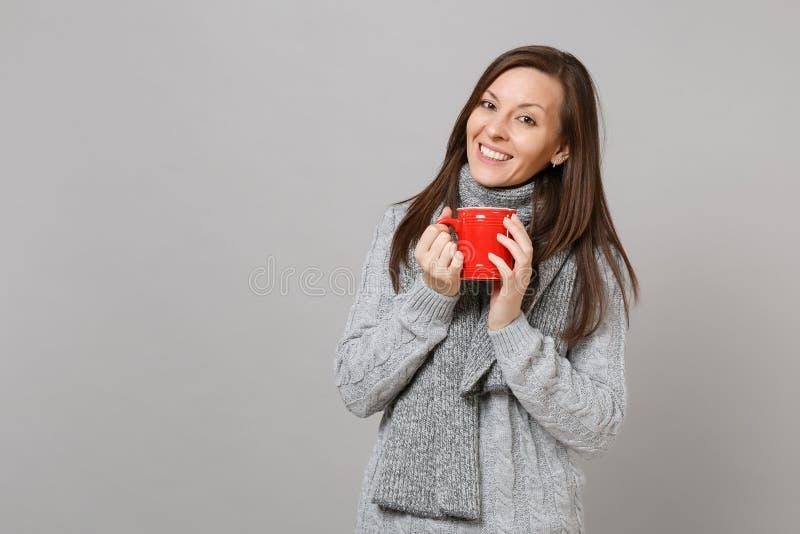 Giovane donna sorridente in maglione grigio, in sciarpa che tiene tazza di caffè rossa o in tè isolato sul fondo grigio della par immagini stock libere da diritti