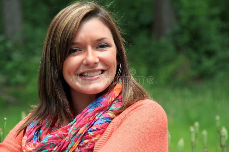 Giovane donna sorridente in maglione variopinto e sciarpa immagini stock