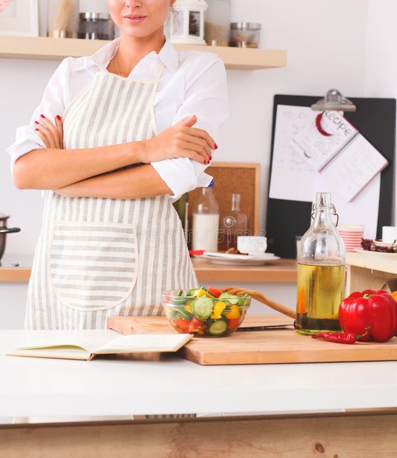 Giovane donna sorridente nella cucina, isolata sul fondo di natale fotografie stock