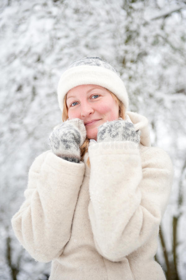 Giovane donna sorridente nella neve fotografia stock