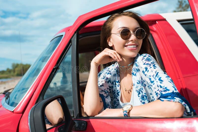 giovane donna sorridente in occhiali da sole in automobile fotografia stock libera da diritti