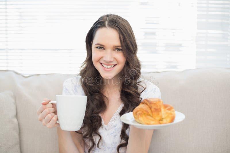 Giovane donna sorridente in pigiami che mangiano prima colazione fotografie stock libere da diritti